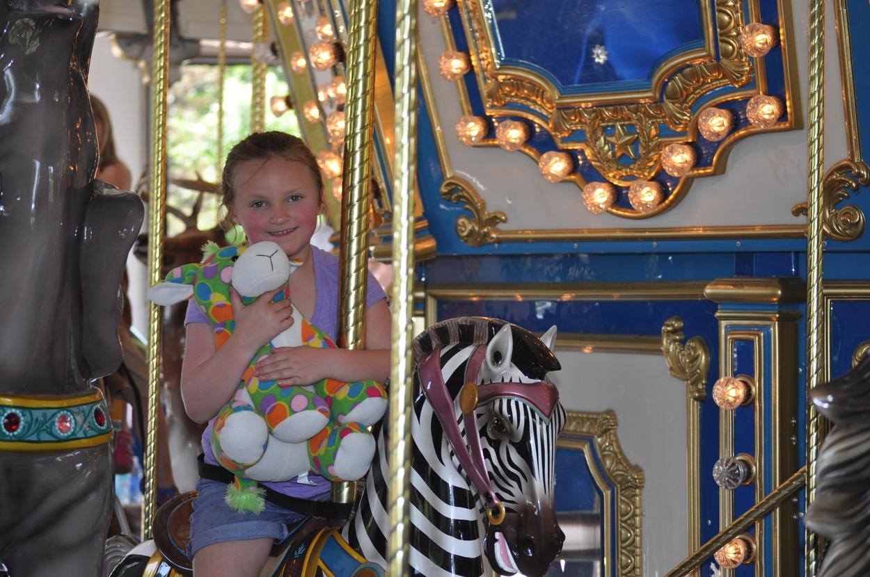 Girl riding carrousel at Great Plains Zoo